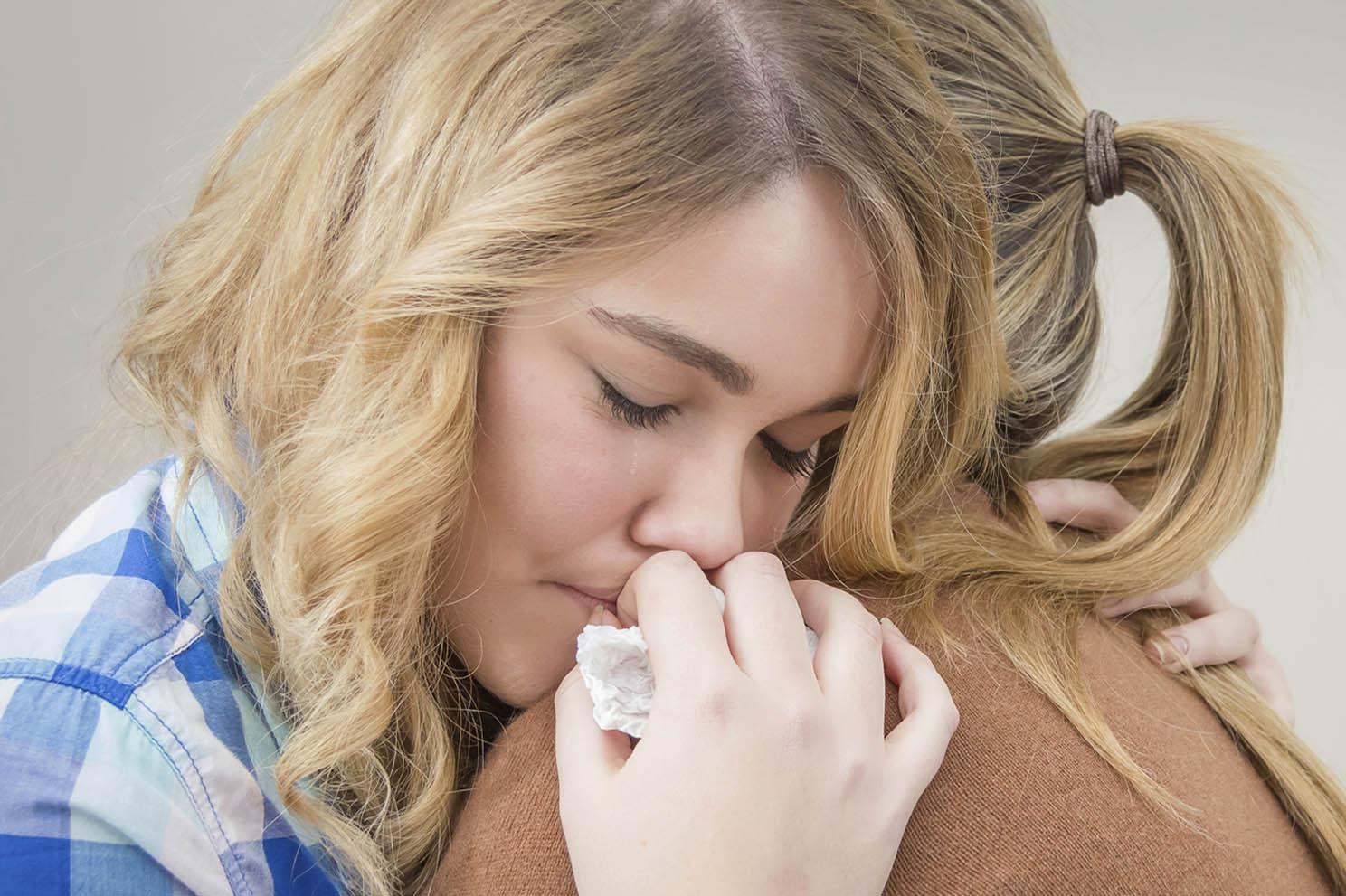 An upset girl hugging an adult